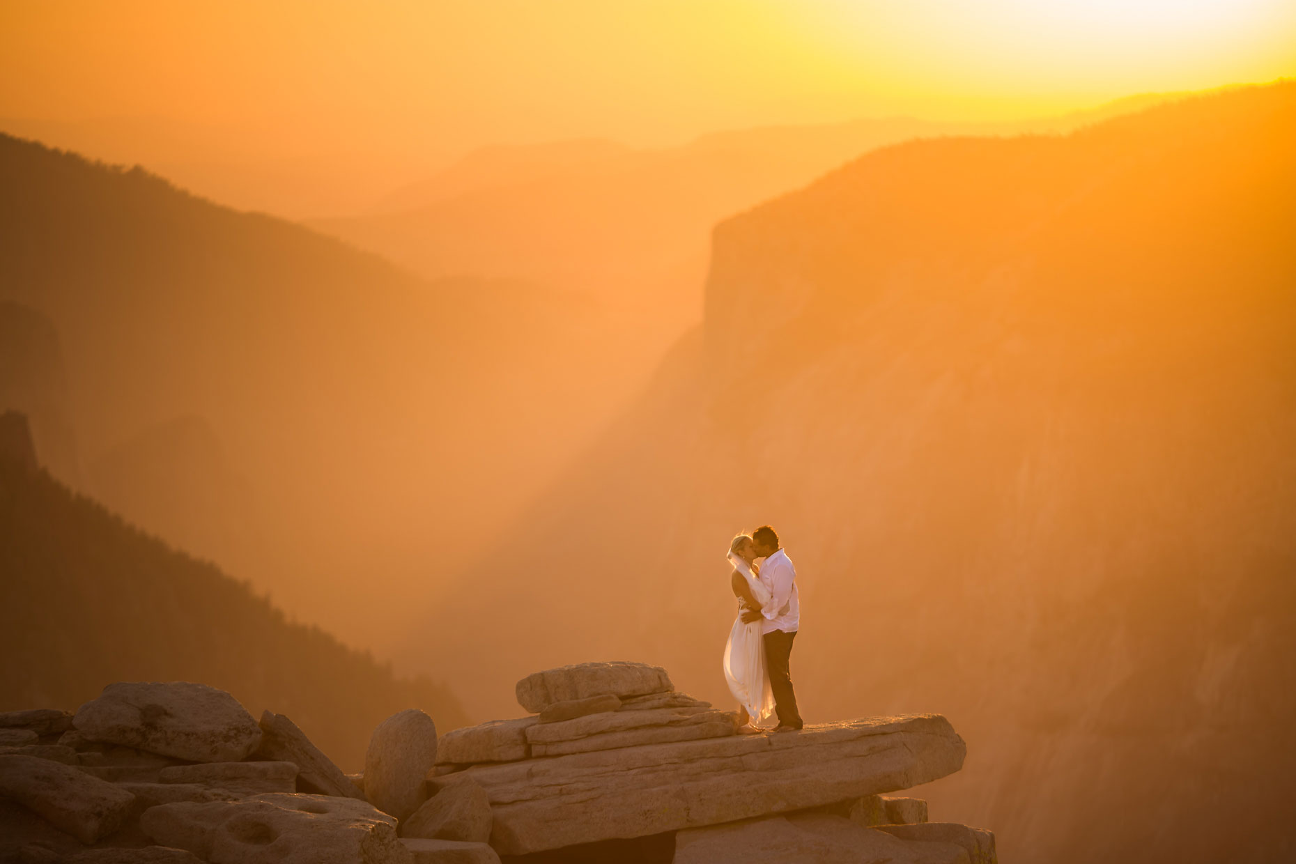 Wedding couple at sunset on Half Dome in Yosemite.