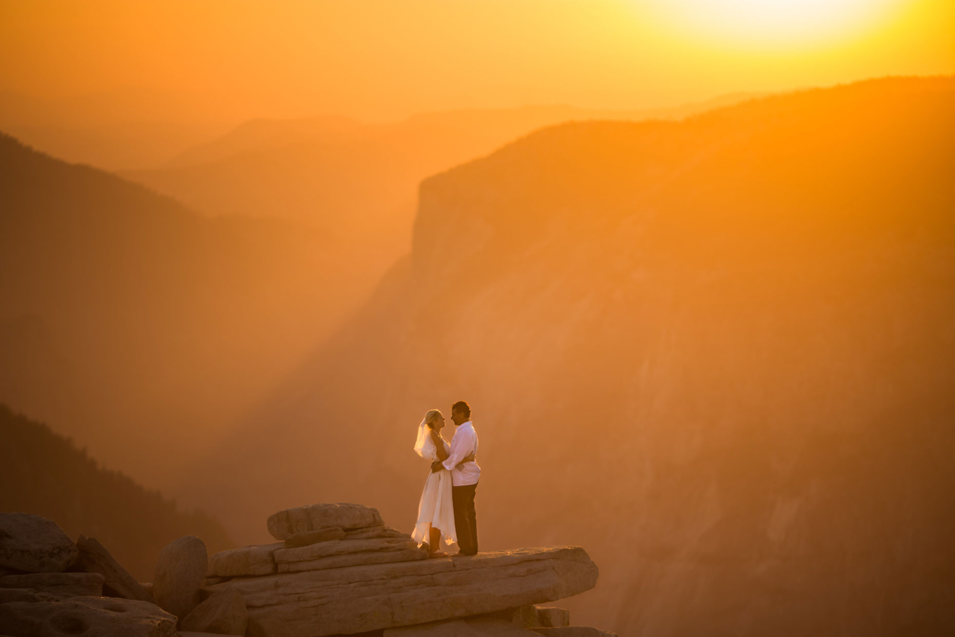 Bride and groom romantic portrait on Half Dome in Yosemite.